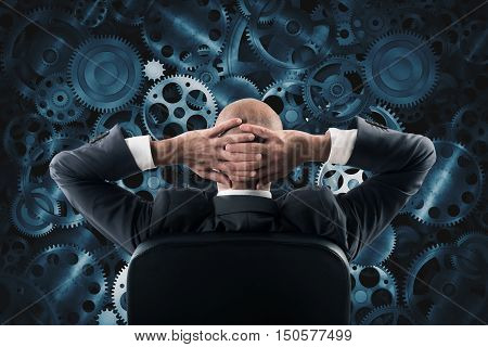 Businessman sitting in a chair watching and analyzing a wall of the gear mechanisms