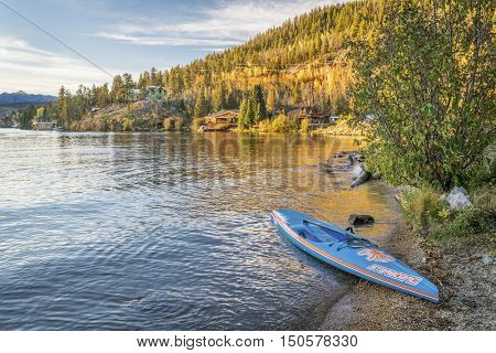 GRAND LAKE,  CO, USA - SEPTEMBER 26: All Star racing stand up paddleboard by Starboard in brushed carbon layout with Werner paddle on a shore of Grand Lake.
