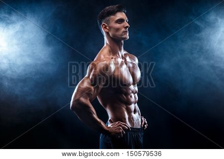 Strong bodybuilder man with perfect abs, shoulders, biceps, triceps, chest.