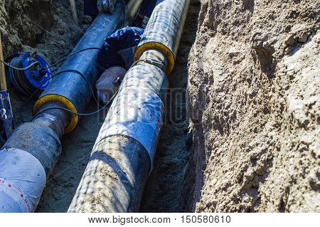 Two Pipes and Welder in the Earthen Trench. Wide Pipes in the Earthen Trench for Heating System