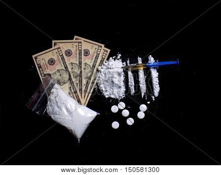 Injection syringe on cocaine drug powder lines and pile, pills, cocaine powder bag and dollar money bills on black background