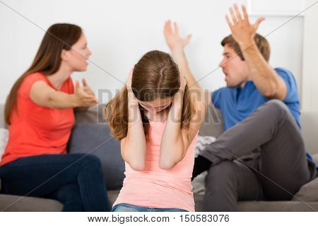 Upset Girl Covering Her Ears In Front Of Parent Having Argument