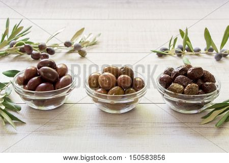 Olives black, green, sun-dried into a bowls next to the olive tree branches on the white wooden background. Three types of olives. Horizontal. Daylight.