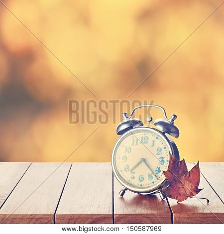 Vintage Alarm Clock On Autumn Season Background