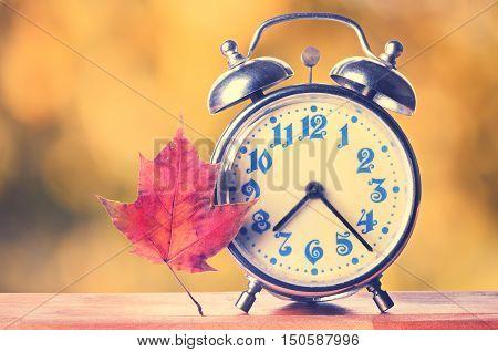Vintage Alarm Clock On Autumn Season Background