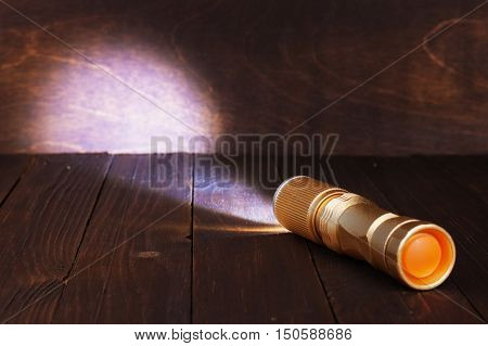Bright LED flashlight shines on the wooden surface.