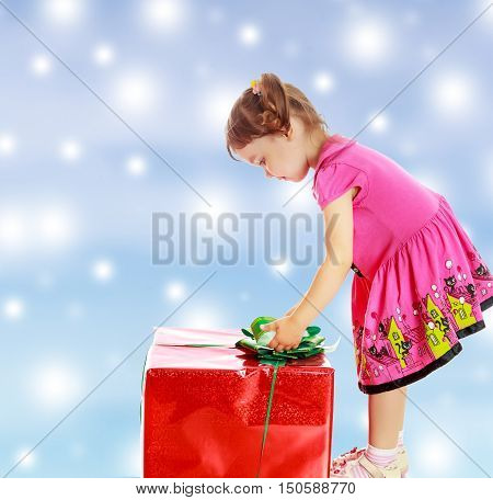 Cute little girl in a pink dress, turned sideways and bent over a large box with a gift. The girl unties the bow.On new year or Christmas blue background with white big stars.