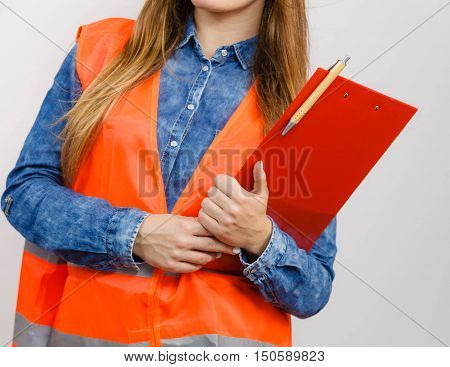 Woman construction worker builder structural engineerin in orange vest holds pen file pad. Safety in industrial work. Studio shot