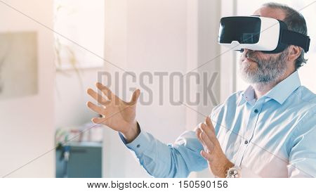 Mature Business Man Wearing Virtual Reality Googles / Vr Glasses To Work With In Modern Office