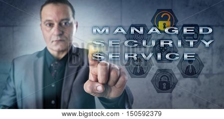 Mature male corporate executive touching MANAGED SECURITY SERVICE on an interactive screen. Information technology concept and computer security metaphor for outsourcing of network security services.
