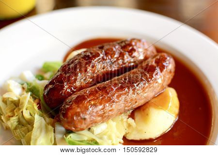 Sausage and mashed potato with seasonal greens served with red wine gravy on a white plate