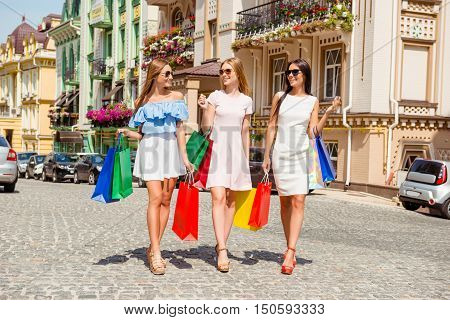 Three Happy Shoppers In Glasses Walking With Packages
