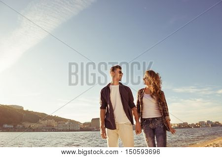 Two Young Happy Smiling Lovers Walking Near The River