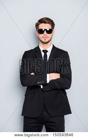 Portrait Of Bodyguard In Black Suit And Glasses With Crossed Hands