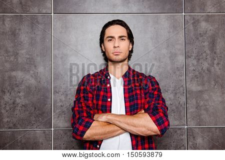 Young Serious Man With Crossed Hands Isolated On Gray Background