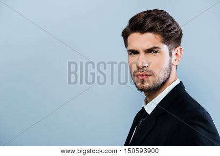 Portrait Of Serious Young Businessmman In Suit On Gray Background