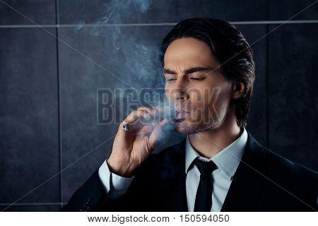 Closeup Portrait Of Brutal Young Man Smoking A Cigar
