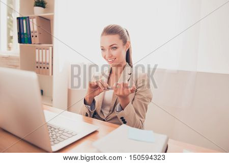 Portrait Of Young Pretty Woman Filing Nails In Office