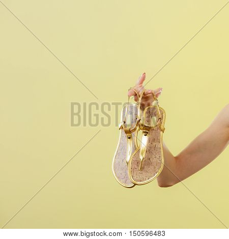 Holidays summer fashion concept. Woman holding golden sandals in hand bright background copy space