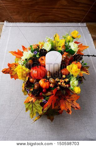 Fall decoration with candle and silk maple leaves vertical. Thanksgiving greeting with fall decor. Fall centerpiece. Thanksgiving background.
