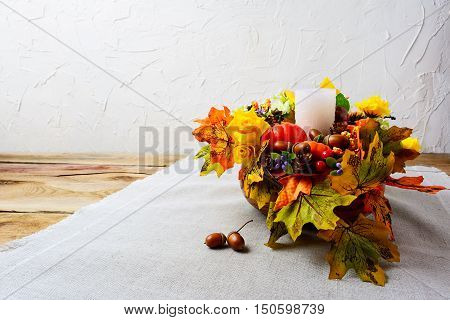 Thanksgiving centerpiece with white candle and silk fall leaves . Thanksgiving background with fall decor. Fall background. Copy space.