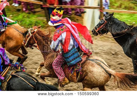 Todos Santos Cuchumatan, Guatemala - November 1 2011: Traditionally dressed drunken jockeys race up & down dirt track on horseback in unique All Saints' Day celebration in highland town