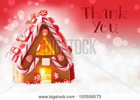 Gingerbread House In Snowy Scenery As Christmas Decoration. Candlelight For Romantic Atmosphere. Red Background With Bokeh Effect. English Text Thank You