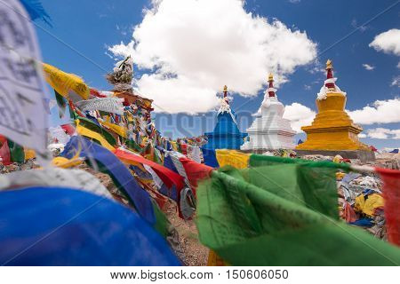 Three buddhist stupa with Buddhist prayer flags with blue sky at Khardongla pass, Leh, Ladakh, India.