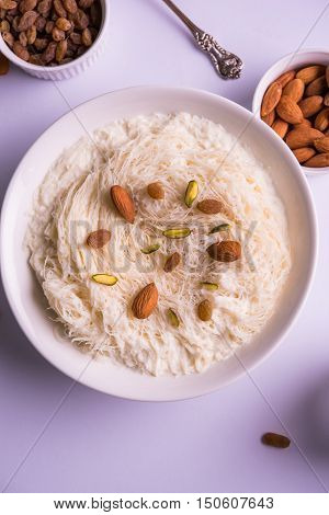 Indian sweet sutarfeni or sutar feni or firni or seviyan or laccha, shredded, flaky-rice-flour roasted in ghee, blended with melted sugar to form a cotton candy, topped with pistachio and almonds