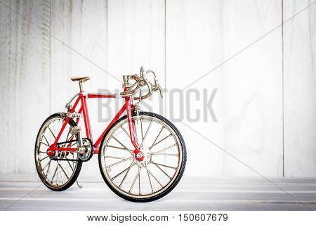 Model bike on the old white wooden floor.