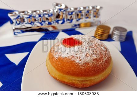 Photo of a white and blue Israeli flag with the star of david with chocolate coins sufganiya and silver menora - objects for the Jewish holiday of Hanukkah.