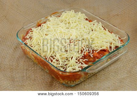 Unbaked prepared casserole dish with turkey, mixed vegetables, pasta, marinara sauce and shredded mozzarella cheese