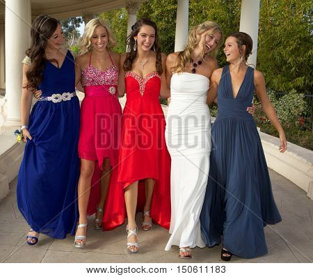 Beautiful Teenage Girls at the Prom.  They are walking and laughing together outside