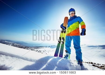 Happy skier stands on the slope with colorful ski on slope backdrop