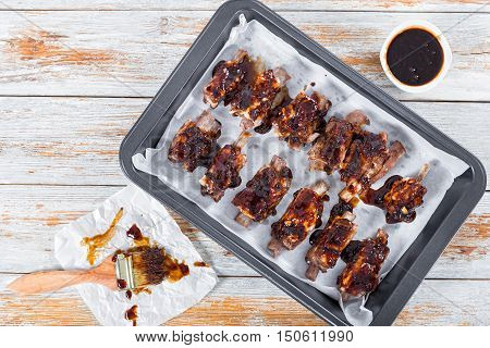 delicious sticky ribs seasoned with a spicy garlic ginger barbecue sauce prepared for grill in roasting pan on white peeling paint planks with basting brush view from above
