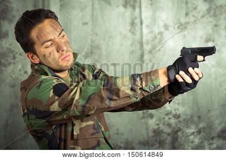 portrait of soldier militar latin man in camouflage uniform pointing a gun to the side