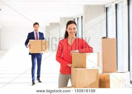 Portrait of confident mid adult businesswoman standing by stacked boxes with male colleague in background at office