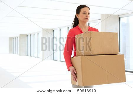 Mid adult businesswoman carrying cardboard boxes in new office