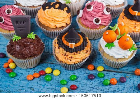 Halloween cupcakes with decorations: Witches hat eyes tombstone and orange pumpkins made from confectionery mastic wooden background