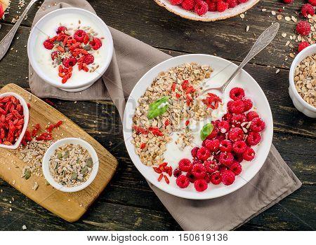 Healthy Breakfast. Muesli, Goji Berries, Yogurt On Rustic Wooden Background.