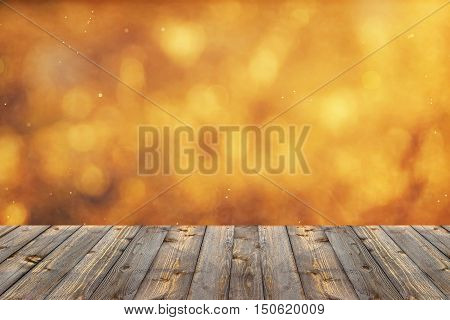 Empty wooden flooring on an blurred golden background with a bokeh.