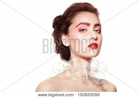 Portrait of young beautiful woman with stylish rose make-up and fancy bubble-glass necklace over white background