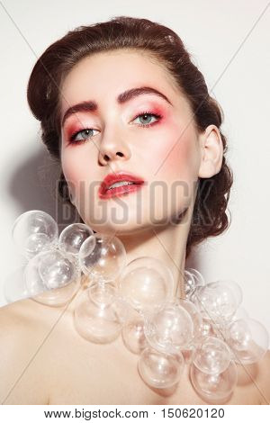 Portrait of young beautiful woman with stylish rose make-up and fancy bubble-glass necklace