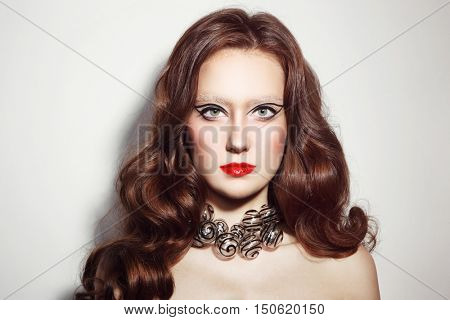 Portrait of young beautiful woman with long curly hair, fancy make-up and stylish glass necklace