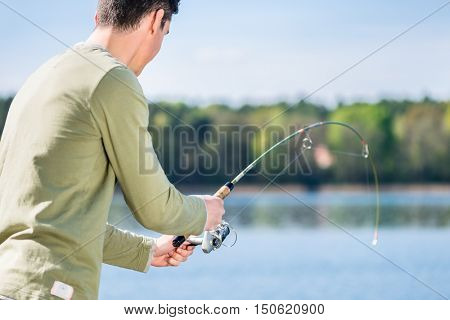 Fisherman at lake fishing for sport trying to hauling a fish in