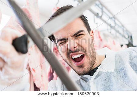 Butcher having fun working in the butchery