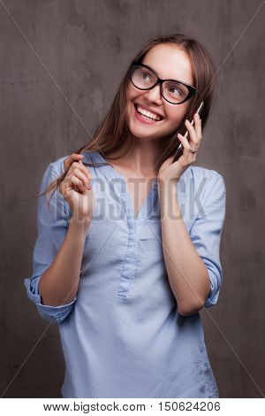 Closeup portrait of beautiful happy young woman with glasses speaking by cellphone near grey background grunge wall