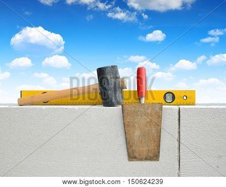 Masonry tools on white brick wall. Bricklaying work.