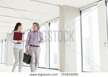 Businessman and businesswoman talking while walking in new office