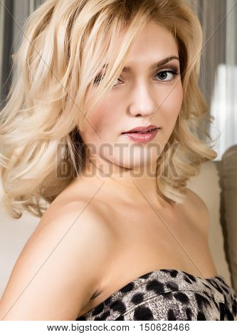 Portrait of a young blond woman with beautiful curling hair and professional make-up